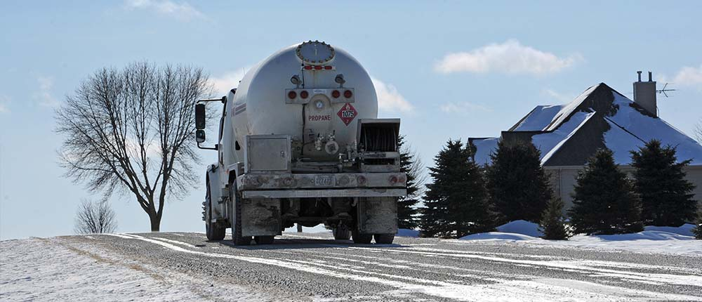 Truck delivering propane to residential home in winter